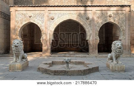 Cairo, Egypt - December 2, 2017: Two white marble lions statues and decorative fountain in front of three adjacent decorated stone arches at the garden of Manial Palace of Prince Mohammed Ali located in Manial district