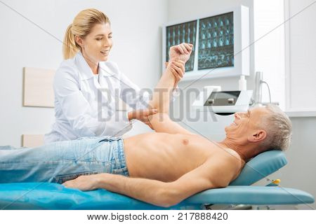 Professional physician. Positive cheerful delighted woman holding her patients arm and smiling doing medical checkup