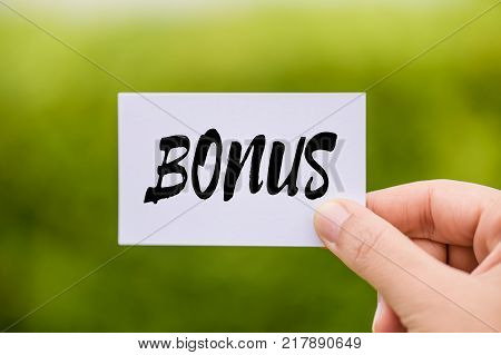 Hand holding Bonus card with green background. Business achievement concept.