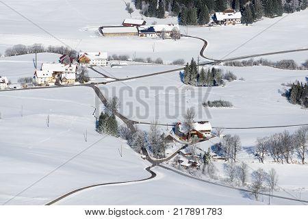 Idyllic rural countryside on snowy winter day. Aerial view of barnyards and farms. Weitnau, Allgau, Bavaria, Germany. Typical bavarian cultured landscape.
