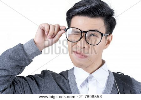 Close up young Asian male student in white shirt and grey jacket hand touching eyeglasses and winking isolated on white background