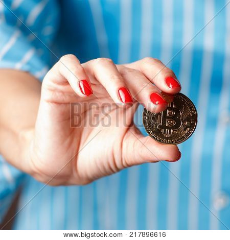 The hand of a girl with a red manicure holds a coin bitcoin. A photo of a close up of hands on a blue background.