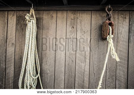 Block And Tackle Pulley. Fisherman's block and tackle pulley system with white rope set against a weathered wooden background.