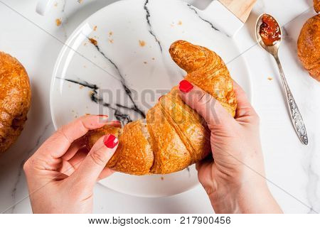 Girl eats homemade continental breakfast croissants coffee. jam on white marble table copy space top view hands in picture
