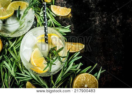 Cold lemonade or alcohol vodka cocktail with lemon and rosemary On a black rusty metallic background copy space top view