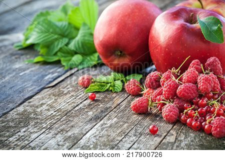 Redcurrant, rasberry and red apples on old wooden table, mix of red color vitamins concept