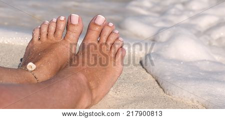 Female toe on sandy beach in caribbean sea waves. Tropical vacation
