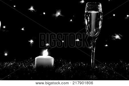 High glasses for champagne. Good New Year spirit. Candles and champagne on the New Year's table. Glasses on the background of dressed up Christmas spruce. Black and white photo
