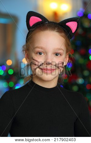 Pretty charming beautiful artistic blond baby girl in Christmas costumes. Beautiful blonde child girl in a carnival costume of a cat.
