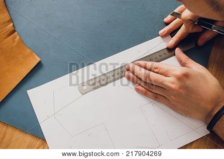 Working day in studio. Man leather worker drawing sketch of purse in notebook on table with leather wallets and tools for sewing. Effective work in leather workshop. Design of fashion leather purse