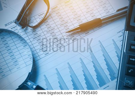 business documents accounting with calculator pen glasses and magnifying glass. concept for financial