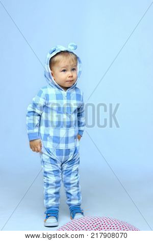 Vertical portrait of cute standing Baby Boy Wearing  on Blue Sleepwear. Image of Sweet Baby Boy, Full-length Portrait of A Child, Cute Toddler With Blue Eyes. Sleepwear  For Child and Baby.