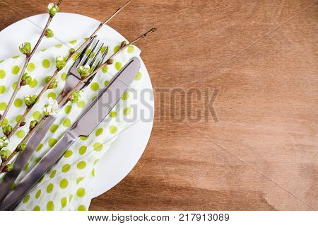 Spring Festive Table Setting with Flowering Branch Cherries Cutlery and Napkin on Wooden Rustic Table. Selective Focus.