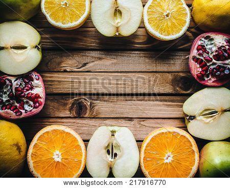 Frame of fresh fruit on wooden background. Multivitamin concept. Autumnal vitamins.