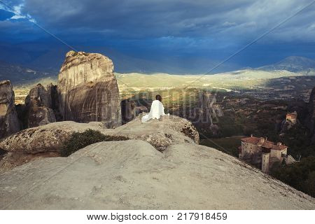 Alone female with cap in the white plaid on the edge of the rock look on the monasteries of Meteora. Female on the rock and monasteries of Meteora in Greece in Thessaly at the early morning