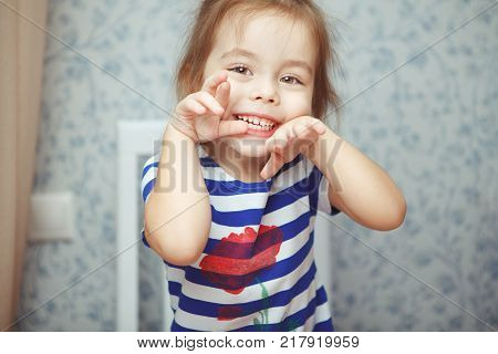 Cute little girl in striped T-shirt makes funny crazy face with open mouth, big brown eyes, and raised arms sits on white wooden chair in room.
