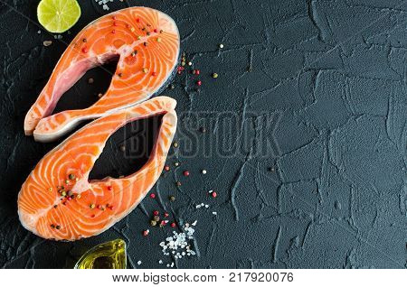 Two fresh raw salmon steaks with pepper corns salt lemon and olive oil on black background with place for text. Healthy food diet concept. Preparation for cooking fish. Top view. Copy space.