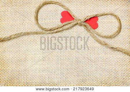 Big bow rope sack with pair red heart paper on brown sack background have copy space for put text