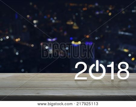 2018 start up business icon on wooden table over blur colorful night light city tower Happy new year concept