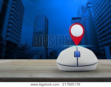 Map pin location button with wireless computer mouse on wooden table over modern office city tower Map pointer navigation concept