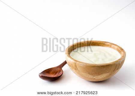 Natural yogurt in wooden bowl isolated on white background. Copyspace