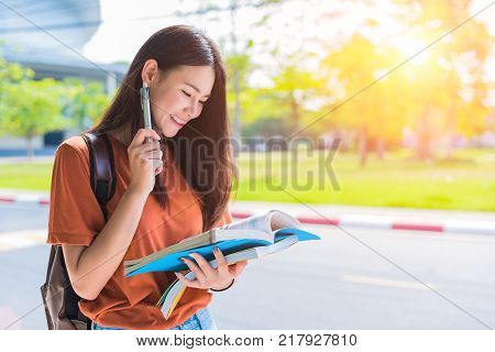 Asian young college woman doing homework and reading books for final examination in campus. University and student concept. Lifestyle and beauty concept. Teenager and Learning theme.