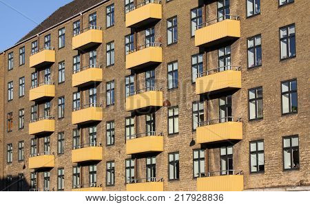 Residential cells of a building with a lot of windows and balconies. The rhythm of the windows. Geometric pattern.