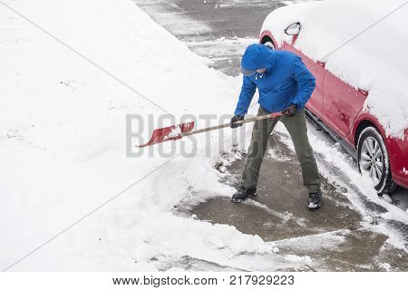 Man Clearing Snow From His Driveway With a Shovel