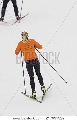 Rear view of a skier in an orange jacket, black pulling sports pants, winter sport