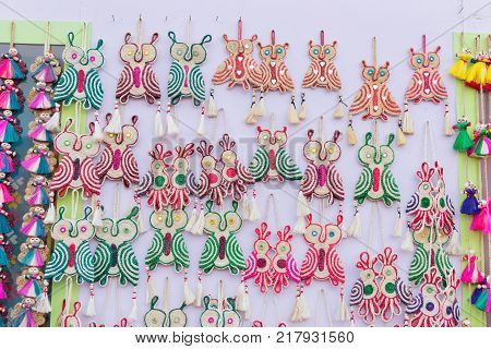 Colorful decorative wall hangings owls made of jute handicrafts on display with white background during the Handicraft Fair in Kolkata - the biggest handicrafts fair in Asia.