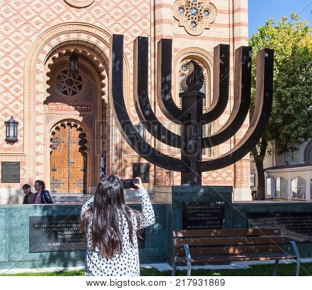 Bucharest Romania October 10 2017 : The tourist photographs a Menorah standing at the entrance to the synagogue Coral in Bucharest city in Romania