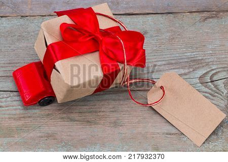 Red toy car delivering gifts box with tag with empty space for a text on wooden background. poster
