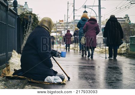Old female beggar holding walking stick wearing a shabby overcoat asking for money on Moscow street in winter