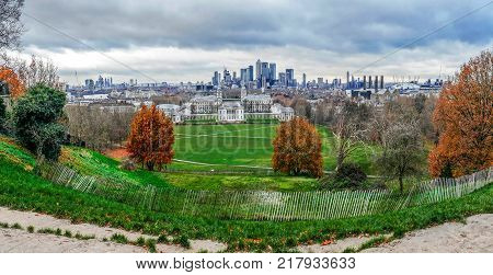 LONDON, ENGLAND - NOVEMBER 272017: Panoramic view with Queen's House from Greenwich Hill with the skyline of Canary Wharf on background. Designed by Inigo Jones the house was completed in around 1636