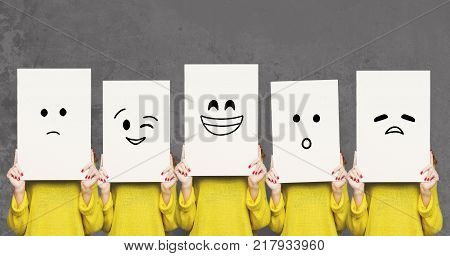 Emotions set. Girl hiding face behind signboard with drawn smileys. Collage of indifferent, winking, happy, surprised, and sad
