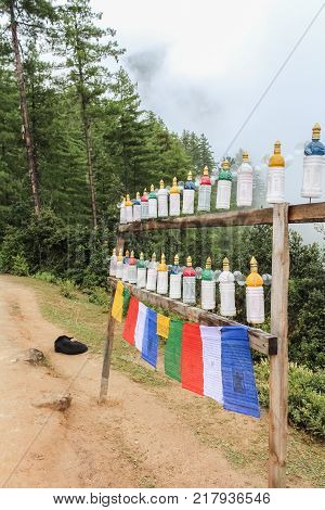 White plastic roadside prayer wheels on the way to Taktshang Palphug Monastery (the Tiger's Nest) Bhutan Asia