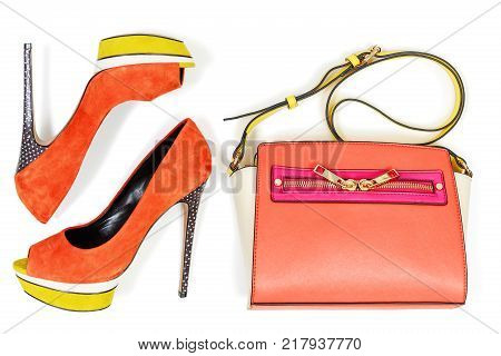Pare of peep toe orange and yellow high hilled platform pump shoes and matching bag isolated on white background top view