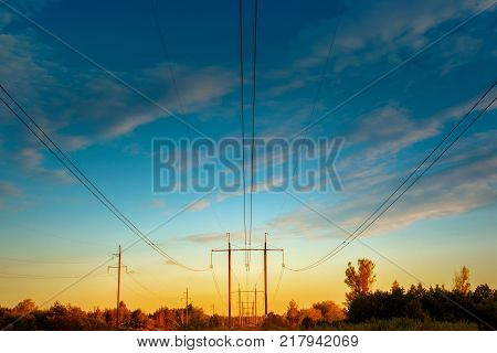 high - voltage power line. Wires and power towers of electricity above the forest at sunset. Supply of energy