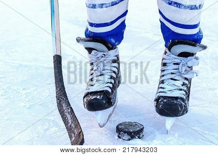 The feet of a young hockey player hockey stick and puck close-up on the background of the ice.