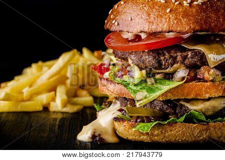 Cheese burger with grilled meat, cheese, tomato and potatoes on dark wooden surface. Fast food template. Real photo. Ideal for advertisement. Close-up. Still life hamburger and French fries