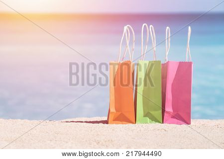 Shopping bags on sand against turquoise caribbean sea water. Tropical celebration on beach