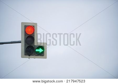 Traffic light with stop signal and green arrow on the background of cloudy sky