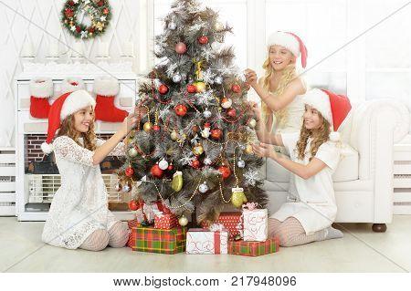 Three girls preparing for Christmas decorating Christmas tree