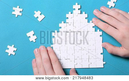White details of puzzle on background. A puzzle is a puzzle from small pieces. Heart shape of the details. Hands folding puzzle in white.