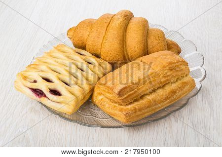 Croissant puff bun and wicker bun with jam in transparent dish on wooden table