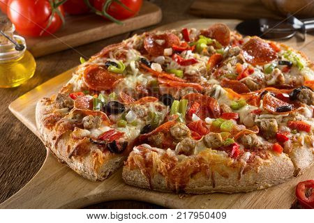 A delicious pizza with pepperoni sausage black olives red pepper green pepper and onions.