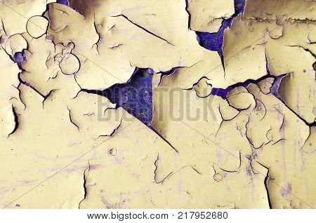 Peeling paint of yellow color on the wooden texture surface. Texture background of peeling paint, closeup of peeling paint texture on the old rough background. Peeling paint texture surface, texture background of yellow peeling paint
