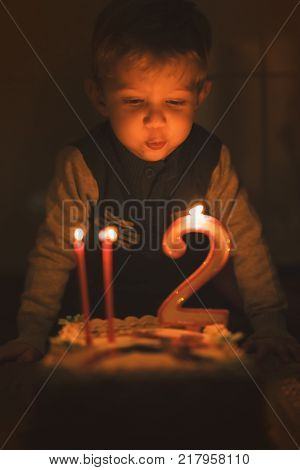 wonderful baby boy is blowing out the candlesonly candle light and low depht of focus for dreaming atmosphereused split toning.