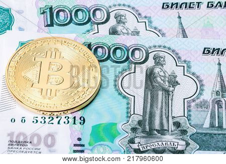 Golden bitcoin on the background of the russian ruble banknotes. Business concept of new virtual money