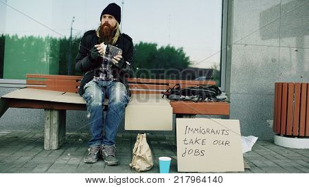 Homeless and jobless european man with cardboard sign eating food on bench at the city street because of immigrants crisis